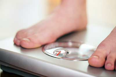 persons feet on a bathroom scale checking weight