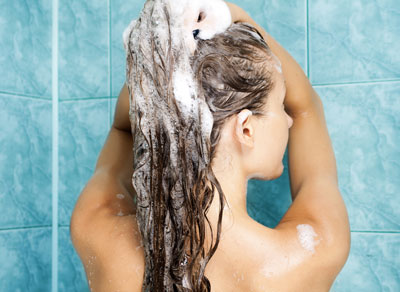 woman shampooing hair in shower