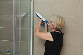 woman caulking shower to prevent mildew