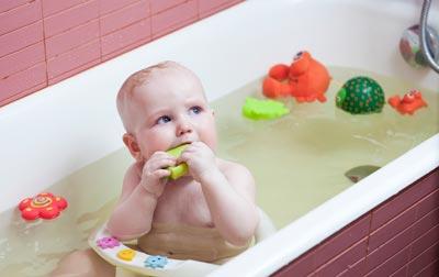 baby sitting up in bath tub with bath toys