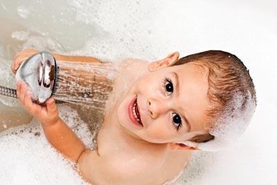boy in bath with shower head