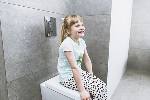 Girl sitting on toilet seat