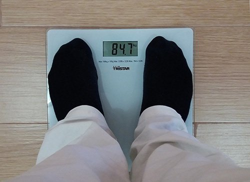 Person wearing socks using a bathroom scale