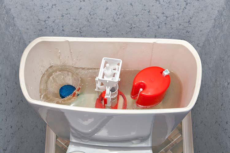 Blue cleaner water soluble tablet falls into toilet flush tank.