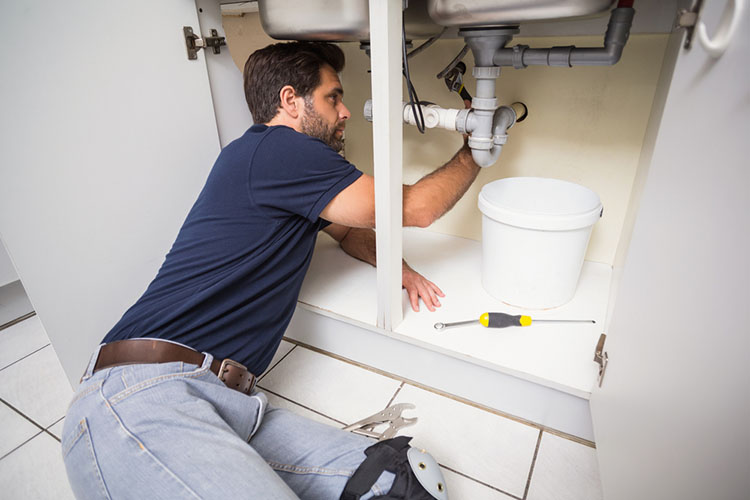Plumber fixing under the sink in the kitchen