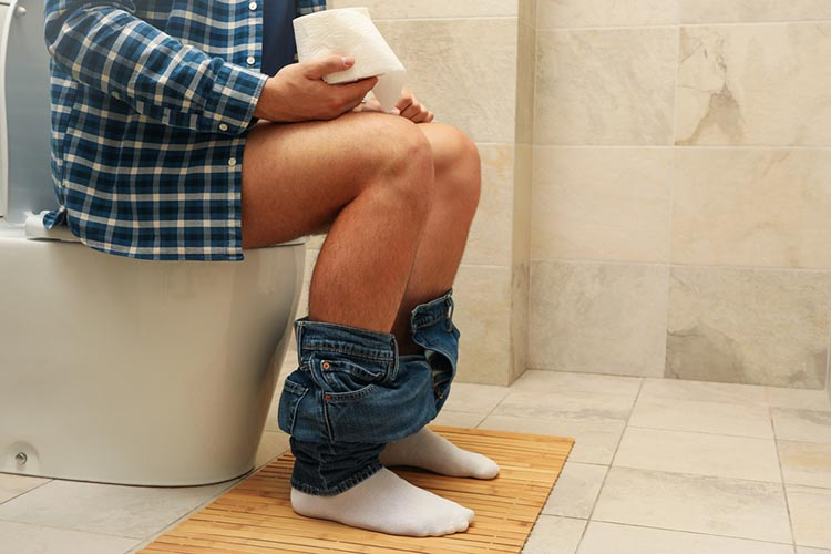 A man sits with his pants down on the toilet