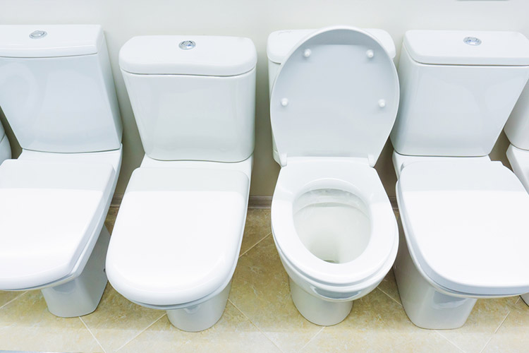 An assortment of ceramic toilets in a plumbing store. Close-up
