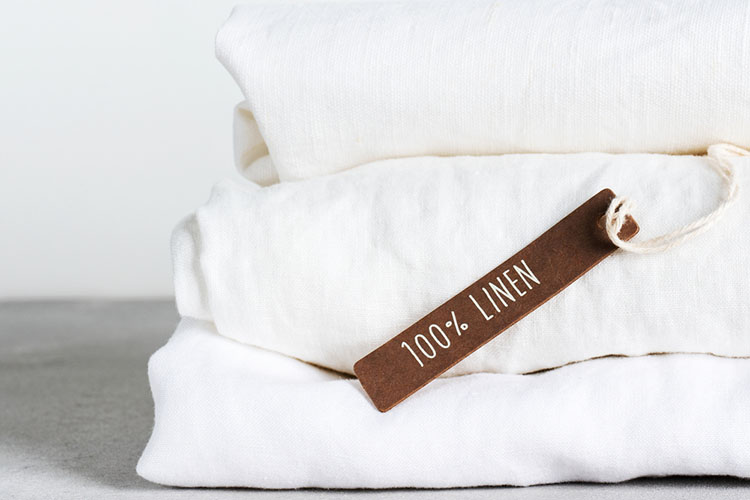 Stack of organic flax with tag of 100% linen on light background