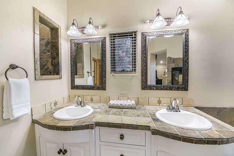 Double vanity sink in a bathroom with stone tiles counter
