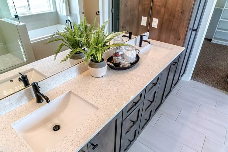 Two sinks on white countertop with plant beside tray of cotton and soap in jars
